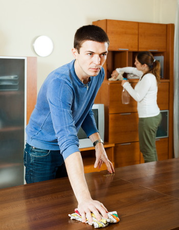 Adult couple dusting wooden furniture at living room photo
