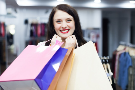 Happy woman with shopping bags at fashion boutique photo
