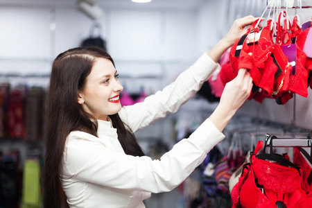 Ordinary woman choosing underwear at clothing store photo