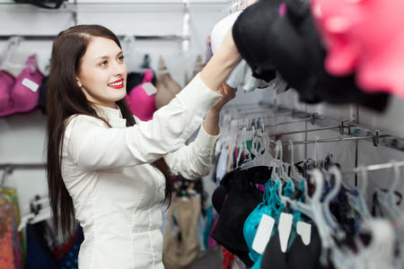 Happy female buyer choosing bra at clothing shop photo