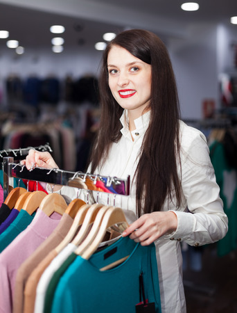 Happy young woman choosing clothes at fashionable shop photo