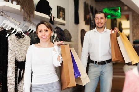 Couple with shop-bags at clothing boutique photo