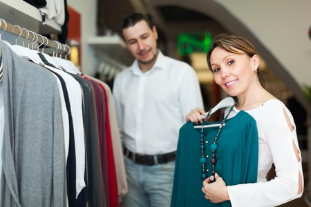 Man with wife choosing clothes at clothing shop photo