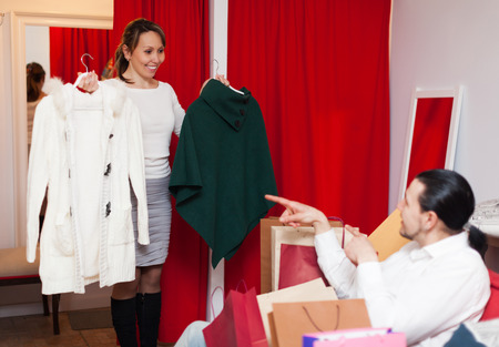 smiling couple choosing jacket at clothing store photo