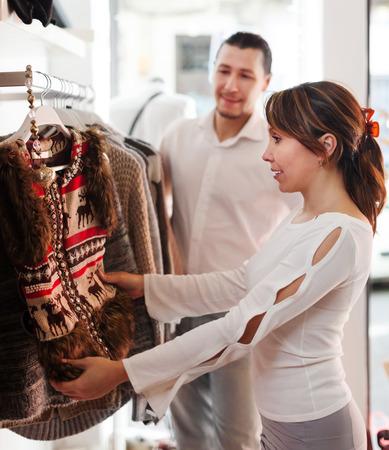 Smiling couple choosing jacket at clothing shop photo
