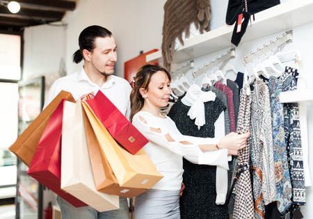 Woman and man choosing dress at boutique photo