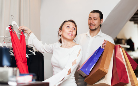 Woman and man with shopping bags choosing dress at clothing shop photo