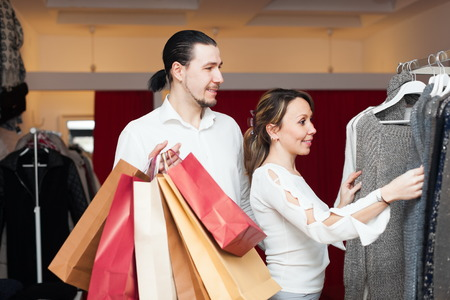 choosing clothes: Joyful couple choosing clothes at boutique