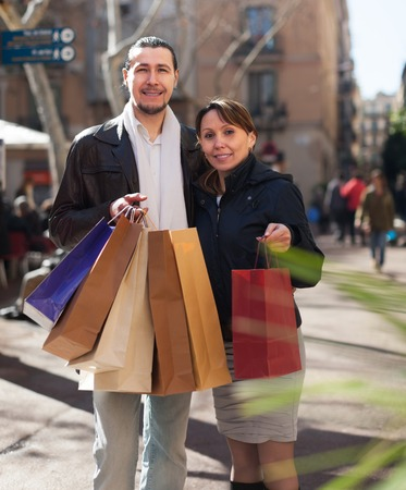 Girl and guy in black jackets with purchases at  street photo