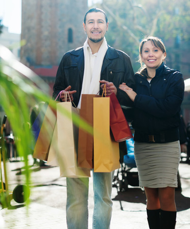 Middle aged couple with shopping bags at  street photo