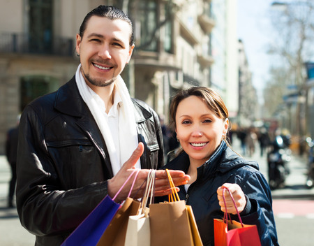 Smiling man and woman with shopping bags at street photo