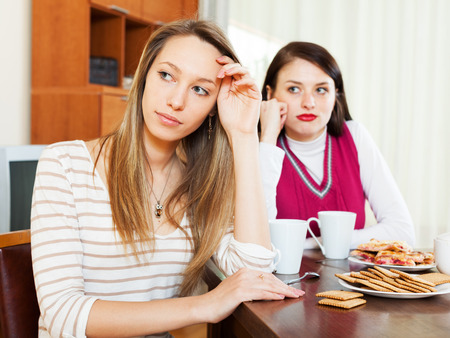 fracas: Two young  women after quarrel at table in home Stock Photo