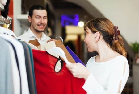 Man and woman choosing clothes at clothing store photo
