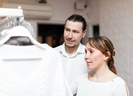 Woman and man looking clothes at boutique photo