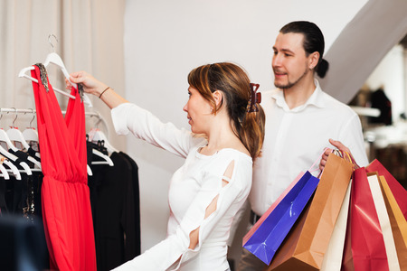 Couple with shopping bags choosing  dress at boutique photo