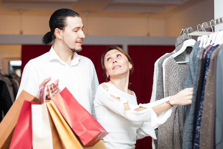 couple with shopping bags choosing sweater at clothing shop photo