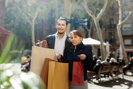 Smiling couple in black jackets with purchases at  street photo