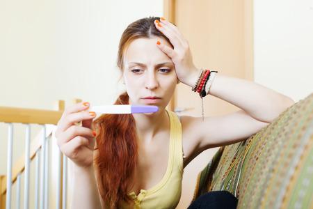 prueba de embarazo: chica seria con la prueba de embarazo en casa interior Foto de archivo