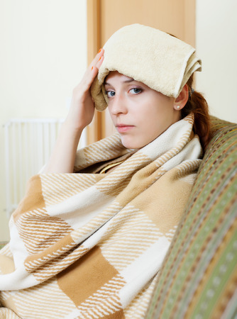 Suffering woman in plaid stupes  towel to her head