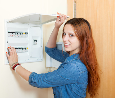 busbar: Smiling woman near power control panel at home