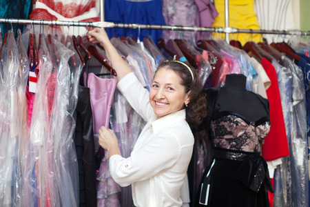 Happy mature woman  chooses evening gown at clothing store photo
