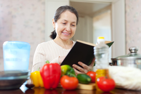 pensive mature woman cooking with cookbook in the kitchen at home photo