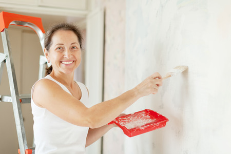 priming brush: Happy mature woman makes repairs at home