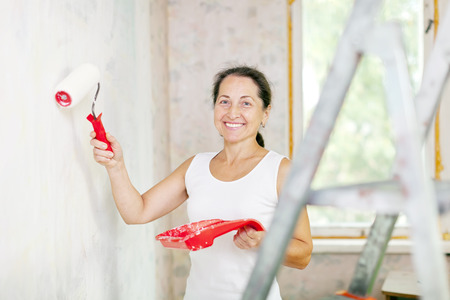 variance: Happy mature woman makes repairs at home