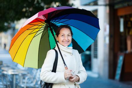 happy seasonable: Outdoor portrait of mature woman with umbrella in autumn