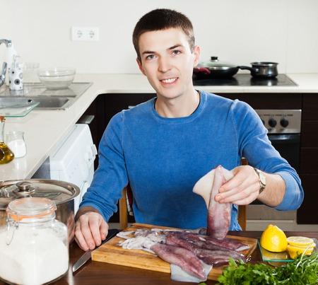 ingridients: smiling man holding raw calamari at home kitchen