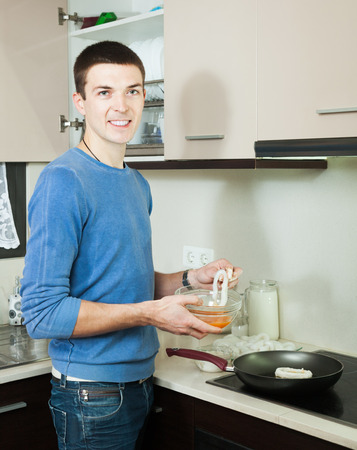panful: Happy man cooking frying squid rings in batter at kitchen Stock Photo