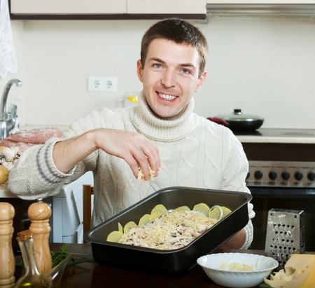 roasting pan: Guy cooking french-style veal. Adding grating cheese in roasting pan.