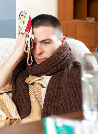 stupes: Sad  young man having headache holding towel on head at home