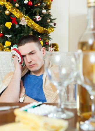 cephalgia:  Man having hangover during christmas holidays at home  Stock Photo