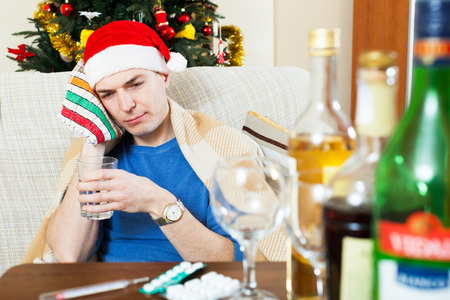 stupes: Young sich man with hangover sitting at the table with glass of water and medication Stock Photo