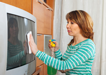 woman in green cleaning TV with cleanser at home photo