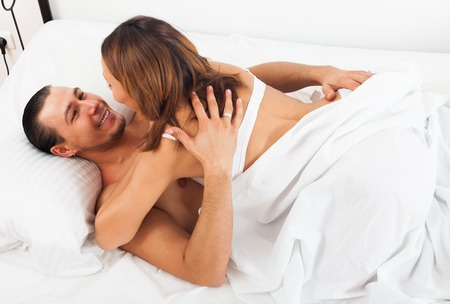 adult sex: Adult couple having sex on bed in home interior Stock Photo