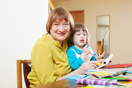 Happy grandmother plays with baby  in home interior Stock Photo - 27210243