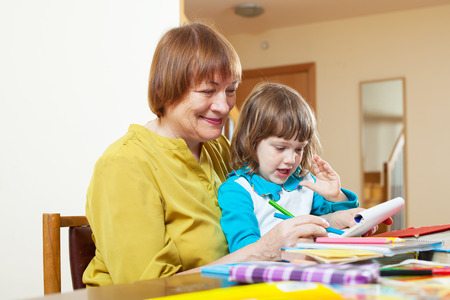 woman and child sketching  on paper at table in home Stock Photo - 27210582