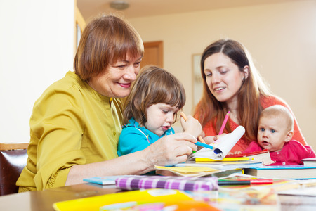 grandmother with daughter and grandchildren sketching  on paper at home. Focus on mature Stock Photo - 27210585