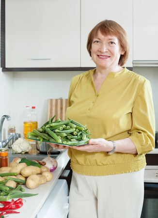 woman cooking vegetables with okra in domestic kitchen Stock Photo - 27210594