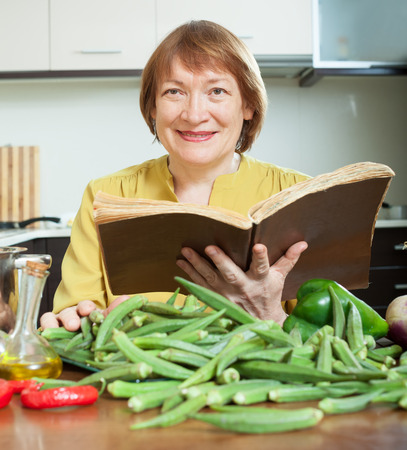 mature woman cooking okra with  cookbook in home kitchen Stock Photo - 27210595