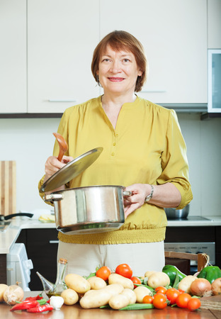 Smiling mature woman cooking  vegetarian lunch with potatoes in domestic kitche Stock Photo - 27210616