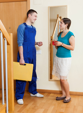 Girl meeting service worker at the door at home photo