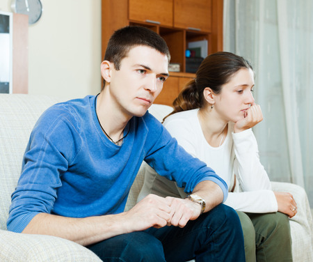 family fight: Family quarrel. Sad guy and woman during quarrel  in living room at home