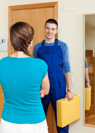 Housewife  meeting repairing engineer at the door at home photo