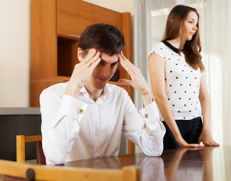 composed: Young couple having serious talking in home interior. Focus on man Stock Photo