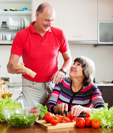 senior man in red and  woman cooking lunch together in  kitchen photo