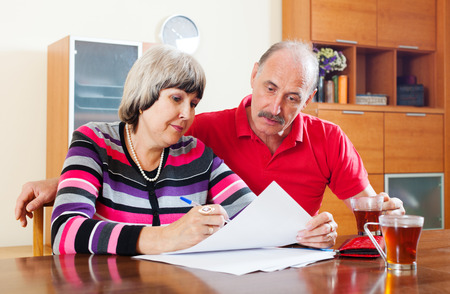 mature couple fills in questionnaire together at home interior Stock Photo