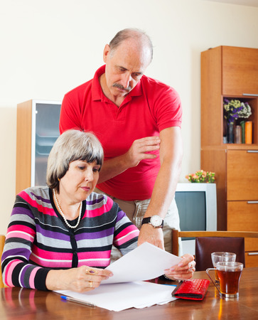 parsimony: serious mature couple calculating family budget